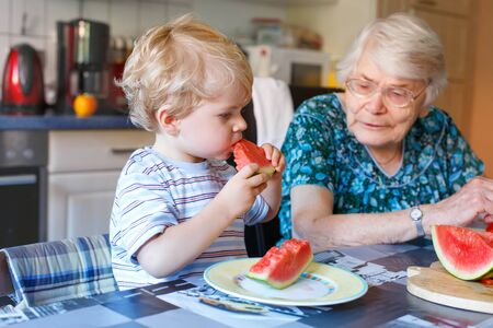 the great grandmother: Cute blond toddler boy and his great grandmother eating watermelon in home kitchen. Happy family of little kid and retired senior woman enjoying healthy fruit. Stock Photo