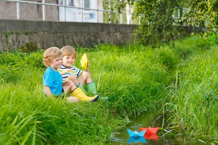 Two little brothers playing with paper boats by a river on warm and sunny summer day. Active leisure for children. Kid boys having fun together outdoors.