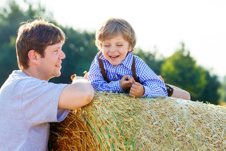 hay field: Happy family of two: Young father and his little son having fun on yellow hay field in summer. Funny kid boy and young man enjoying summertime Stock Photo