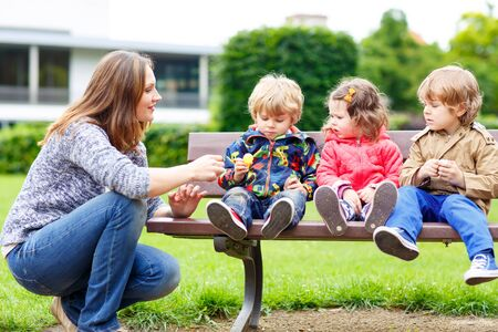 three children: Mother and her three children in summer park, two little kid boys and adorable girl eating together chocolate, outdoors