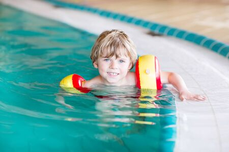 beautiful boy: Adorable little kid boy with swimmies having fun with swimming in an indoor pool. Active and fit leisure for children. Stock Photo
