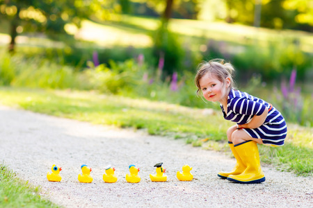 Adorable little kid girl playing in forest playground with yellow rubber ducks. Cute child wearing rain boots. Active leisure with kids.