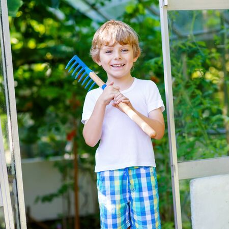 greenhouse and ecology: Smiling little kid boy watering plants and vegetables with can and working with garden hoe in greenhouse. Preschool child helping on sunny summer day. Family, garden, gardening, lifestyle