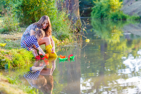 Young beautiful woman and her little daughter playing together with paper boats in a river. Creative leisure with kids. Reklamní fotografie