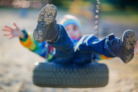 outdoors: Funny kid boy having fun with chain swing on outdoor playground. child swinging on warm sunny spring or autumn day. Active leisure with kids. Selective focus Stock Photo