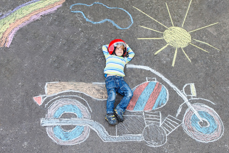 having fun: Creative leisure for children: Funny little child of four years in helmet having fun with motorcycle picture drawing with colorful chalks. Children, lifestyle, fun concept.