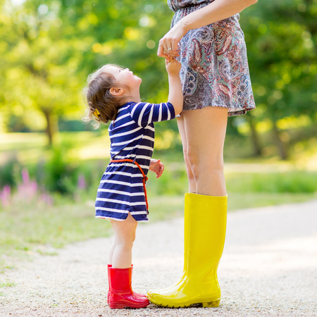 fun in the sun: Young mother and little adorable child girl in rubber rain boots having fun together, family look. Little girl in red boots. Long legs of woman.