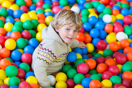 playcentre: Happy little kid boy playing at colorful plastic balls playground high view. Funny child having fun indoors.