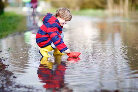 alone boy: Funny little kid boy in rain boots playing with paper ship by a puddle on warm spring day. Active leisure for children. Child having fun outdoors.