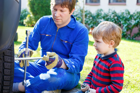 pneumatic tyres: Little blond kid boy and his father changing wheels on car with pneumatic wrench. Man in uniform teaching his son working with tools.