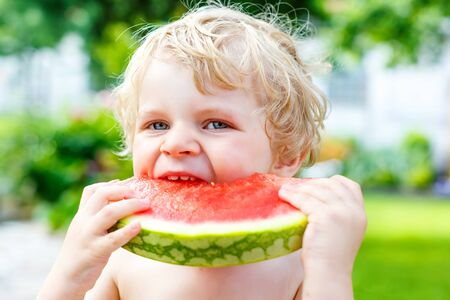 kindergarden: Funny little toddler boy with blond hairs eating watermelon in outdoor kindergarden. Kid tasting healthy snack. Healthy food for children.