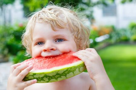 beautiful boy: Funny little toddler boy with blond hairs eating watermelon in summer garden. Kid tasting healthy snack. Healthy food for children.