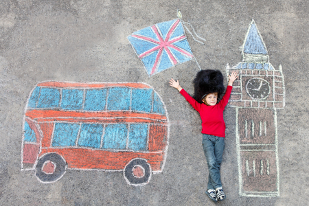 drawing large: Happy little kid boy in british queens guard soldier uniform having fun with London picture drawing with colorful chalks. With Big Ben, Union Jack and red bus.