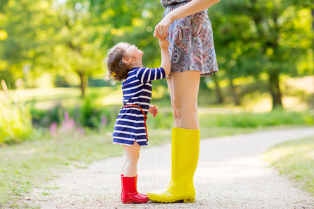 the mother: Young mother and little adorable child girl in rubber rain boots having fun together, family look. Little girl in red boots. Long legs of woman.