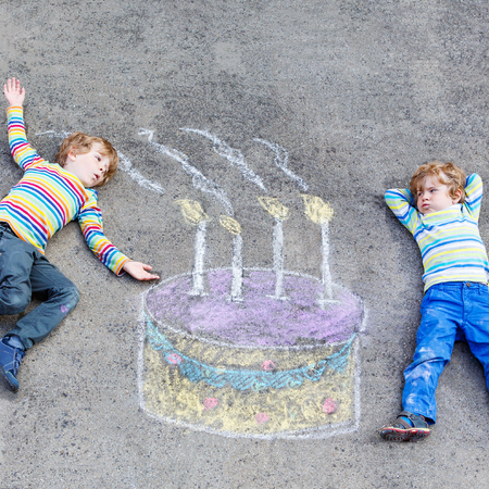 kids having fun: Two happy little kids having fun with big birthday cake picture drawing with colorful chalks. Creative leisure for children outdoors in summer. Kids blowing candles.