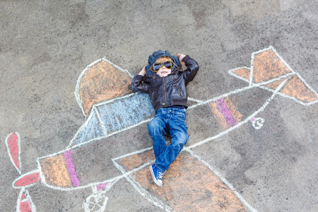 people having fun: Funny little kid boy flying by a plane picture painting with colorful chalk. Creative leisure for children outdoors in summer.