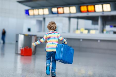 Schattige kleine jongen jongen met blauwe koffer op een internationale luchthaven. Gelukkig kind wating voor de vlucht en gaat op vakantie.