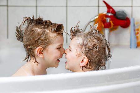 bath: Happy siblings: Two little twins children playing together with water by taking bath in bathtub at home. Kid boys having fun together.