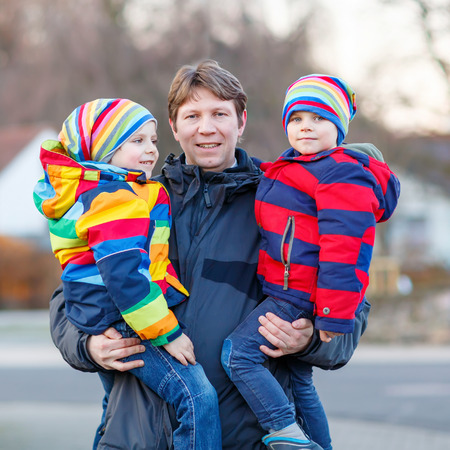 winter park: Active father holding his children, little funny kids boys on arm, on cold day. Man and boys walking together in a park in spring, autumn or winter. Happy, joyful family