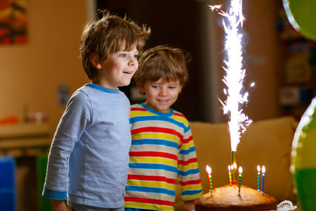 4 5 year old: Beautiful kids, little boys celebrating birthday and blowing candles on homemade baked cake, indoor. Birthday party for children. Happy twins about fireworks