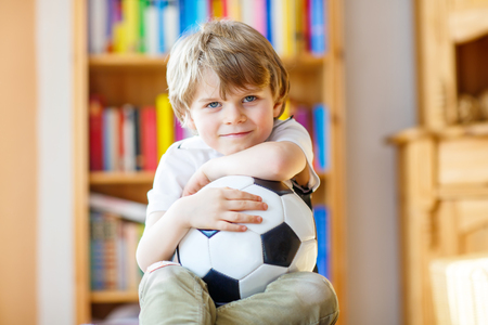 Little blond preschool kid boy with ball watching soccer european cup game on tv. Funny child fan having fun and cheering winning football team. Champions league concept. Stock Photo