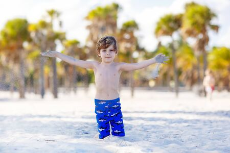 key biscayne: Beautiful blond little kid boy having fun on Miami beach, Key Biscayne. Happy cute child playing with sand and running near ocean.