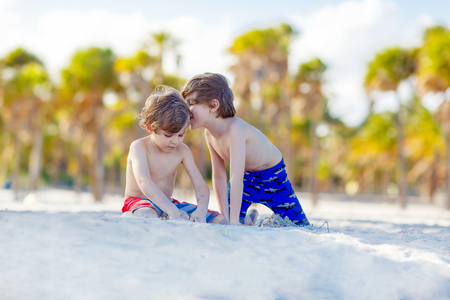 key biscayne: Two little kids boys having fun on tropical beach, happy best friends playing with sand, friendship concept. Siblings brothes in swim trousers. Key Biscayne, Miami, Florida. Stock Photo