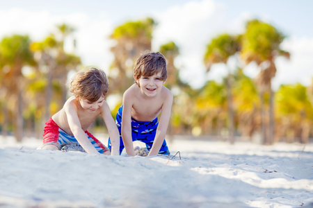 key biscayne: Two little kids boys having fun on tropical beach, happy best friends playing with sand, friendship concept. Siblings twins in swim trousers. Key Biscayne, Miami, Florida.