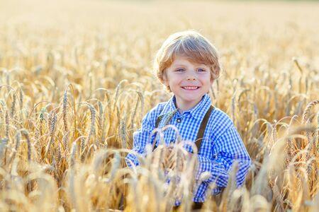 bermudas: Divertido niño pequeño niño en ropa bávaras tradicionales alemanas, pantalones cortos de cuero y comprobar camisa, caminando felizmente a través de campo de trigo cerca de la pila de heno o paca. Al aire libre activa de ocio con los niños el día de verano caliente.