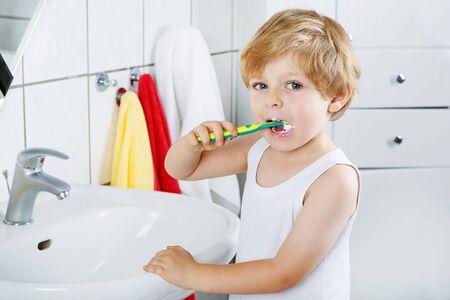 rubia ojos azules: Pequeño muchacho rubio aprendizaje cepillarse los dientes en el baño doméstico. Cabrito que aprende cómo mantenerse saludable. Concepto de salud. Foto de archivo