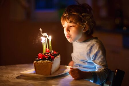 4 5 year old: Adorable five year old kid boy celebrating his birthday and blowing candles on homemade baked cake, indoor. Birthday party for children.