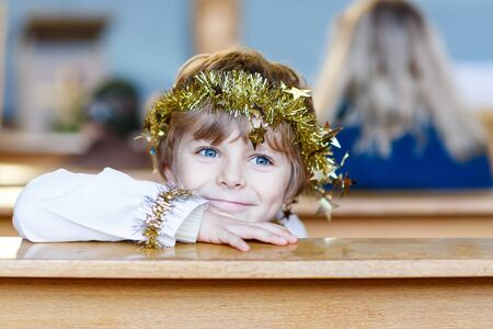 christmas story: Beautiful little kid boy as an angel in Christmas story in a church. Happy adorable blond child with lights and xmas tree on background.