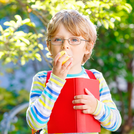 Cute little kid boy with glasses, books, apple and backpack on his first day to school or nursery. Child outdoors on warm sunny day, Back to school concept Stock Photo