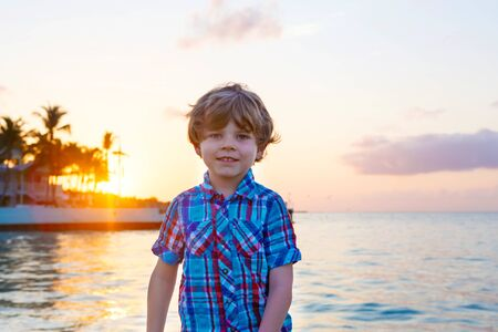 Portrait of cute blond preschool kid boy at sunset near ocean. Happy little child smiling at the camera. With palm trees on background