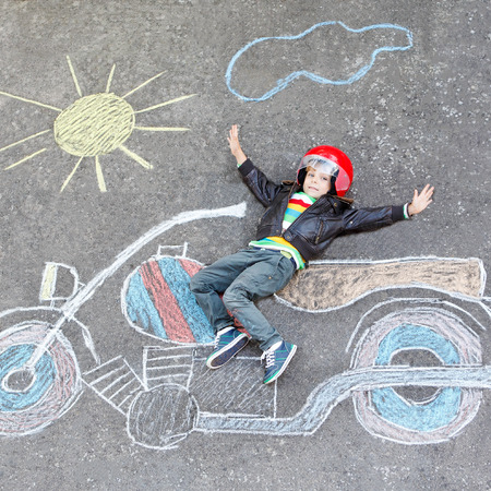 having fun: Creative leisure for children: Happy little child of four years in helmet having fun with motorcycle picture drawing with colorful chalks. Children, lifestyle, fun concept.