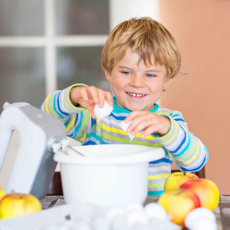 cake mixer: Cute funny blond kid boy of 4 years baking apple cake in domestic kitchen. Happy child having fun with working with mixer, flour, eggs and fruits.