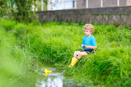 Active happy boy playing with paper boats by a river on warm and sunny summer day. Active leisure for children. Kid having fun outdoors.