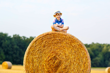 Adorable little kid boy in traditional German bavarian clothes, leather shorts and check shirt. Child sitting on hay stack or bale. Active outdoors leisure with children on warm summer day.