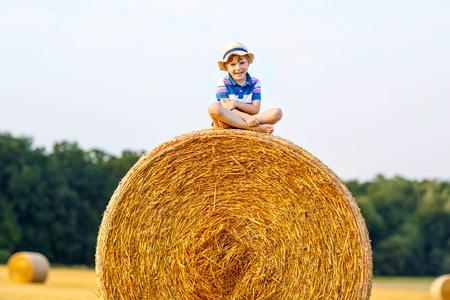 bermudas: Adorable niño pequeño niño en la ropa bávaras tradicionales alemanes, pantalones cortos de cuero y la camisa. Niño que se sienta en la pila de heno o fardo. ocio activo al aire libre con los niños en el día de verano.