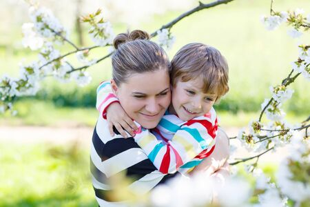 family outdoor: Little cute boy and young mum hugging in blooming cherry garden in spring. Happy family celebrating mothers day.