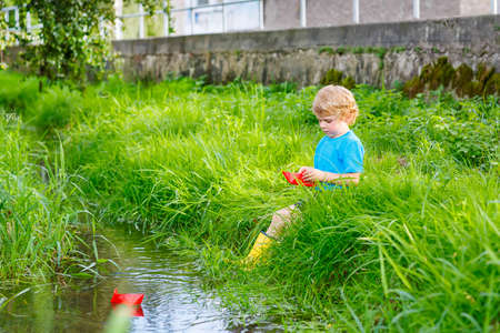 funny cute little boy playing with paper boats by a river on warm and sunny summer day. Active leisure for children. Kid having fun outdoors.