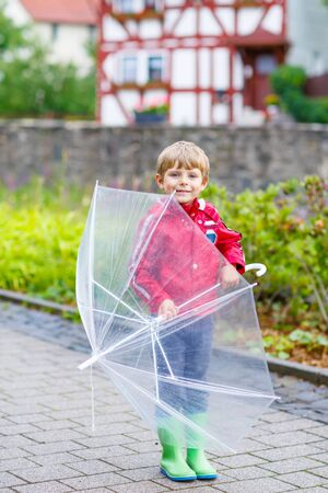 Little blond kid boy walking with big umbrella outdoors on rainy day. Child having fun and wearing colorful waterproof clothes and rain boots. Stock Photo