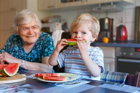 the great grandmother: Cute blond toddler boy and his great grandmother eating watermelon in domestic kitchen. Happy family of little kid and retired senior woman enjoying healthy fruit. Stock Photo