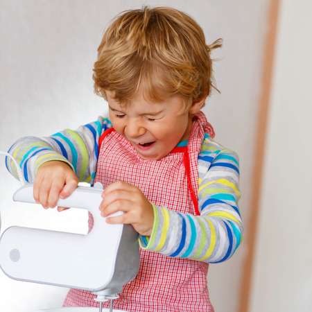 cake mixer: Cute funny blond toddler kid boy baking apple cake and muffins in domestic kitchen. Happy child having fun with working with mixer, flour, eggs and fruits at home. Stock Photo