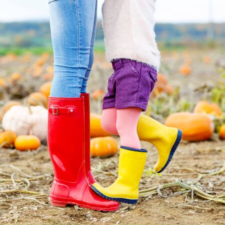 gum boots: Legs of young woman and her little kid girl daugher in rainboots. Woman in red gum boots, child in yellow shoes. On pumpkin field, outdoors.