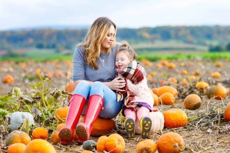 Young mother and daughter sitting on pumpkins on patch. Traditional family festival with children, thanksgiving and love concept. Happy girls hugging