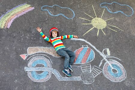 having fun: Happy little kid boy  in helmet having fun with motorcycle picture drawing with colorful chalks. Children, lifestyle, fun concept. child dreaming of future and profession.