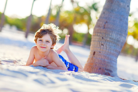 key biscayne: Adorable active little kid boy having fun on Miami beach, Key Biscayne. Happy cute child relaxing and enjoying sunny warm day near palms. Stock Photo
