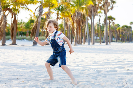 key biscayne: Adorable active little kid boy having fun on Miami beach, Key Biscayne. Happy cute child playing and dancing near palm trees on sunny warm day.
