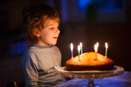 five year old: Adorable five year old kid boy celebrating his birthday and blowing candles on homemade baked cake, indoor. Birthday party for children.